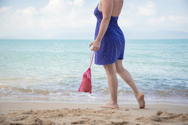 Uma mulher segura uma sacola de compras de rede e fica de pé à beira-mar em uma praia de areia
