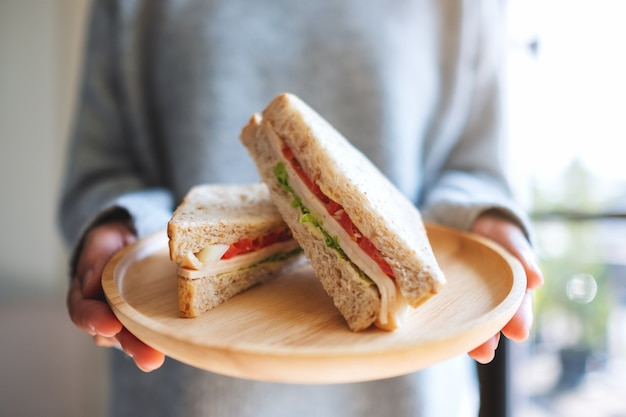 Uma mulher segurando dois pedaços de sanduíche de trigo integral em um prato de madeira