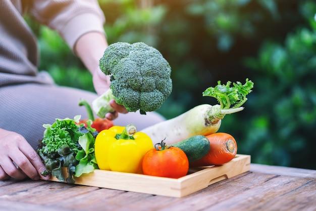 Uma mulher segurando e colhendo vegetais frescos de uma bandeja de madeira sobre a mesa