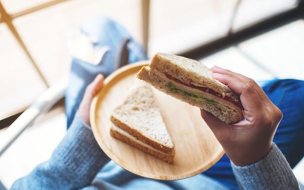 Uma mulher segurando e comendo dois pedaços de sanduíche de trigo integral em um prato de madeira