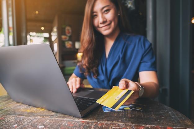 Uma mulher segurando e dando um cartão de crédito a alguém enquanto usa um laptop