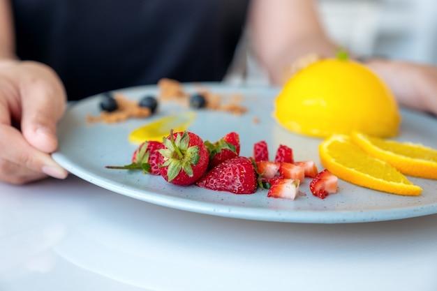 Uma mulher segurando e mostrando um prato de bolo de laranja com uma mistura de frutas em um café