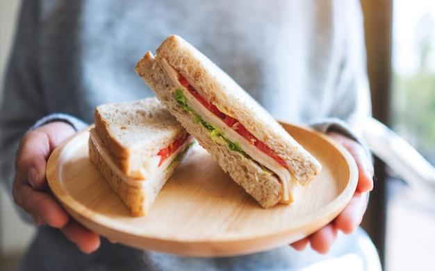 Uma mulher segurando e servindo dois pedaços de sanduíche de trigo integral em um prato de madeira