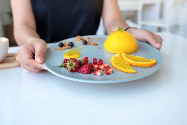 Uma mulher segurando e servindo um prato de bolo de laranja com uma mistura de frutas em um café