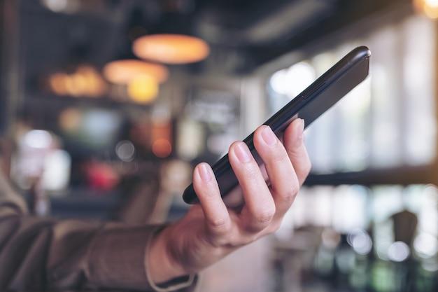 Uma mulher segurando e usando um telefone inteligente preto com desfoque de fundo em um café