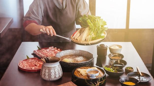 Uma mulher segurando legumes em panela quente por pinças com carne wagyu e kurobuta em fatias em shabu.