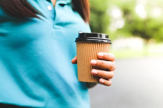 Uma mulher segurando o copo de papel de café.