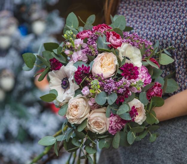 Uma mulher segurando um buquê de flores cor de rosa e branco na mão