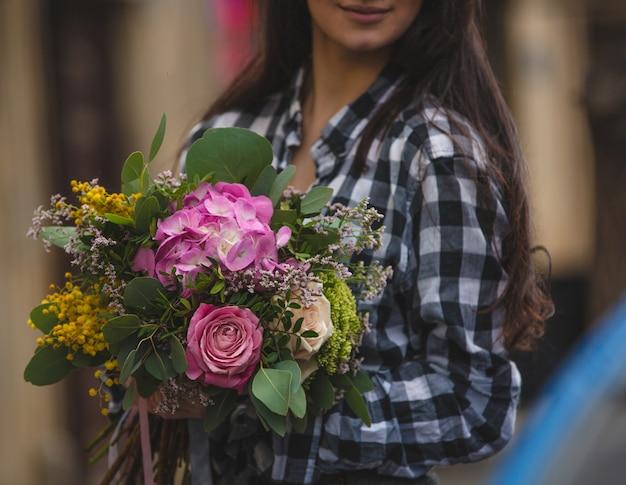 Uma mulher segurando um buquê de flores misturadas em tons de rosa na mão em uma vista de rua