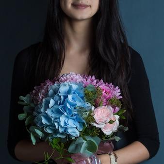 Uma mulher segurando um buquê de flores na mão