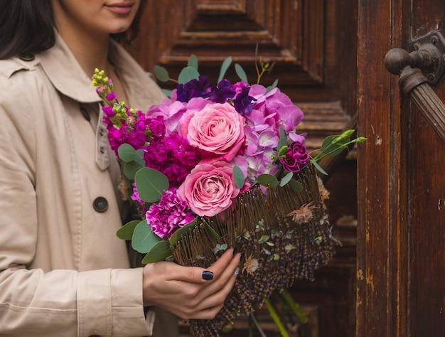 Uma mulher segurando um buquê de rosa, violetas, roxas peônias e rosas na mão