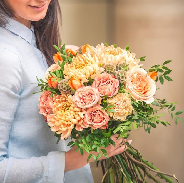 Uma mulher segurando um buquê de rosas corais e peônias na mão