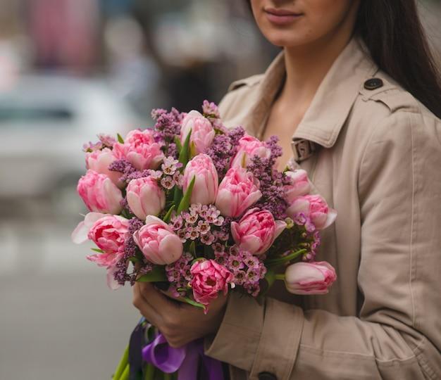 Uma mulher segurando um buquê de tulipas cor de rosa uma sirene na mão