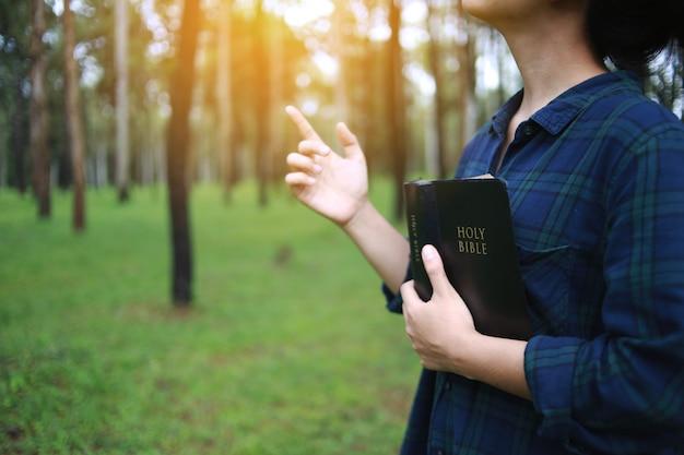 Uma mulher segurando um livro da bíblia e orou a deus.