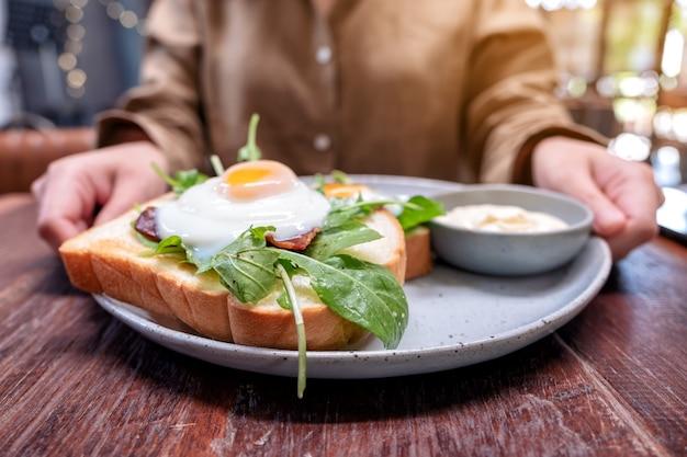 Uma mulher segurando um prato de sanduíche de café da manhã com ovos, bacon e creme de leite na mesa de madeira