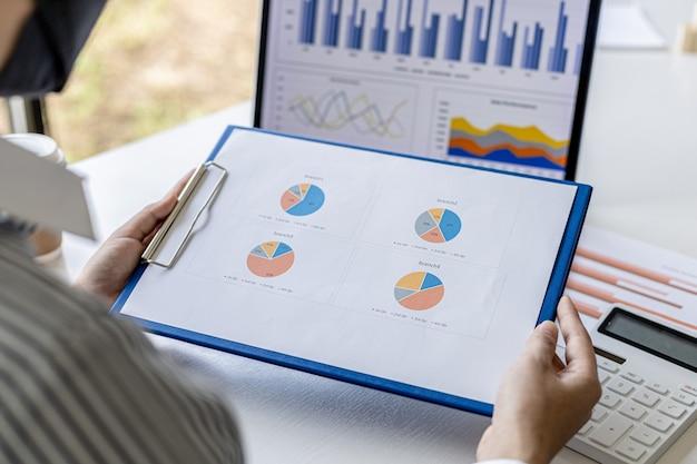 Uma mulher segurando um resumo de vendas, o gerente de vendas está olhando para o documento de resumo de vendas mensal e resumindo-o para pagar as comissões do vendedor. conceito de gestão de vendas.