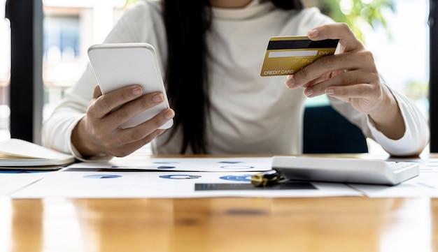 Uma mulher segurando um smartphone e um cartão de crédito, ela está fazendo compras online por meio de um aplicativo de smartphone, pagando pagamentos com cartão de crédito. ideias de compras online com cartão de crédito.