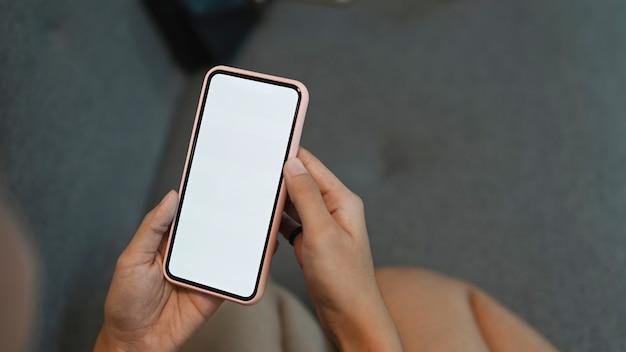 Uma mulher segurando um telefone inteligente e sentada no sofá.