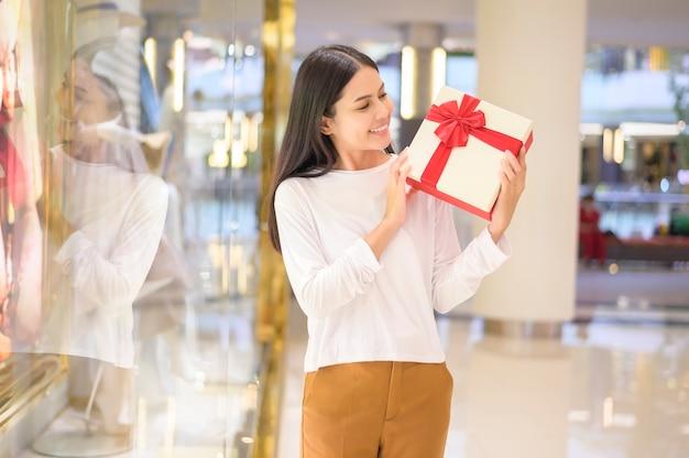 Uma mulher segurando uma caixa de presente em shopping center, conceito de ação de graças e natal.