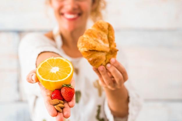 Uma mulher segurando uma laranja e mais frutas na mão e, na outra, um croissant - escolhendo o estilo de vida e o conceito de dieta