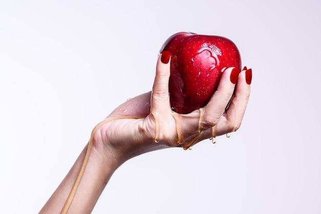 Uma mulher segurando uma maçã vermelha e água correndo através do conceito saudável
