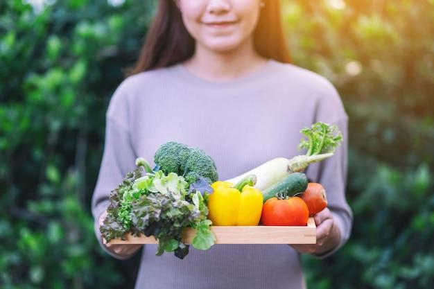 Uma mulher segurando uma mistura de vegetais frescos em uma bandeja de madeira