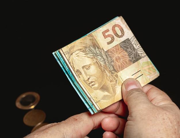 Uma mulher segurando uma nota de banco real brasileira