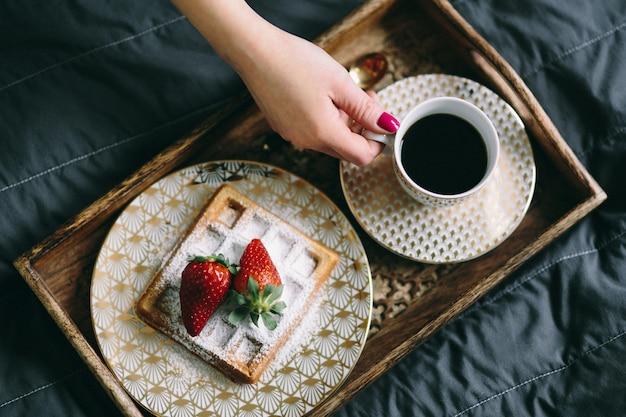 Uma mulher segurando uma xícara de café sobre uma bandeja