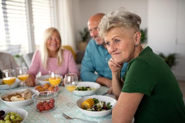 Uma mulher sênior com amigos, festejando dentro de casa, comendo à mesa.