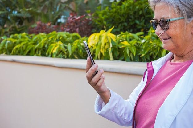 Uma mulher sênior em pé ao ar livre lendo a mensagem em seu telefone inteligente