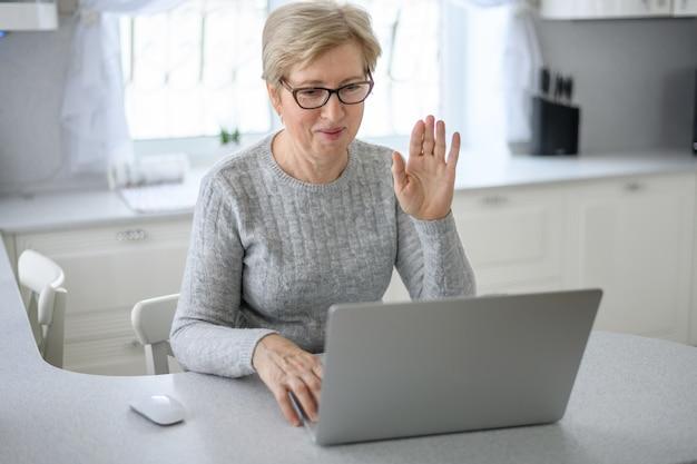Uma mulher sênior trabalha em casa usando tecnologia moderna na vida cotidiana.