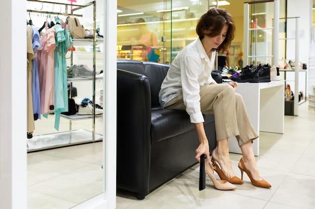 Uma mulher senta no sofá, experimenta e escolhe sapatos de salto alto em uma loja.