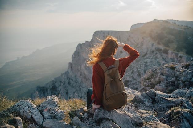 Uma mulher senta-se à beira de um penhasco, um viajante turístico olha o pôr do sol