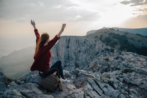 Uma mulher senta-se na beira de um penhasco, um viajante turístico olha o pôr do sol