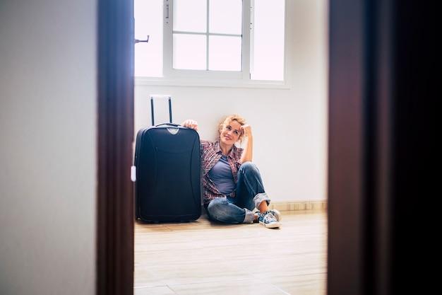 Uma mulher senta-se sozinha dentro de uma casa vazia com bagagem - conceito de pessoas de compradores de hipoteca de casa nova - senhora imobiliária relaxando dentro de casa