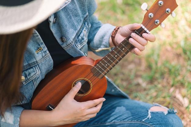 Uma mulher sentada e tocando ukulele ao ar livre
