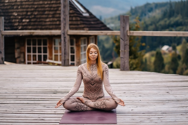 Uma mulher sentada em posição de lótus, de manhã, ao ar livre.