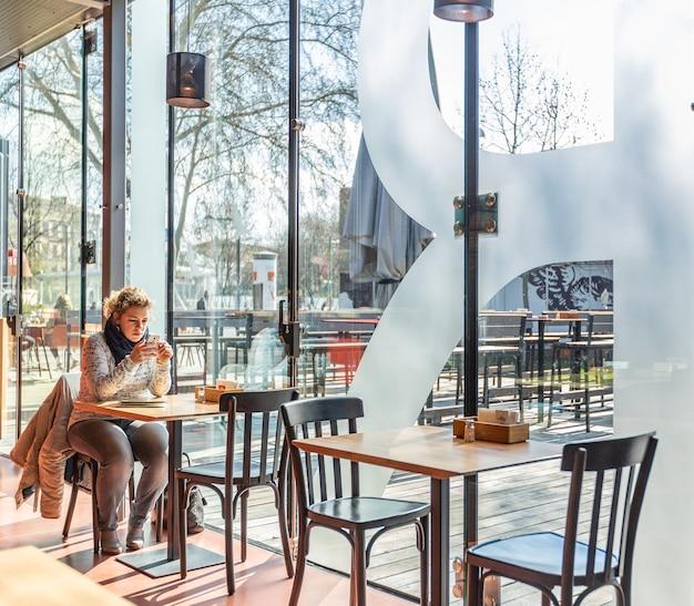 Uma mulher sentada em um restaurante usando seu telefone enquanto espera seu café da manhã