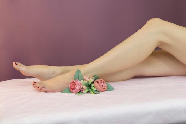 Uma mulher sentada em um sofá com as pernas elegantemente levantadas