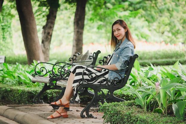 Uma mulher sentada em uma cadeira no parque