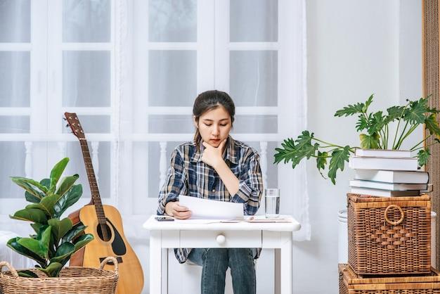 Uma mulher sentada em uma mesa analisa o documento e está estressada.