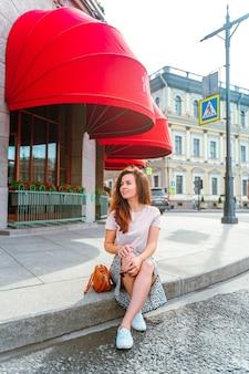 Uma mulher sentada na calçada sob o toldo vermelho em são petersburgo em um dia ensolarado