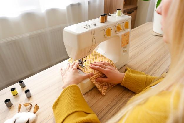 Uma mulher sentada na máquina de costura