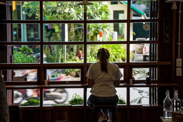 Uma mulher sentada no bar sozinho desfrutar de sua sobremesa no café.