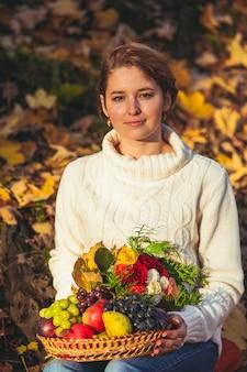 Uma mulher sentada no chão coberta com folhas de outono e segurando uma cesta de outono com frutas e flores