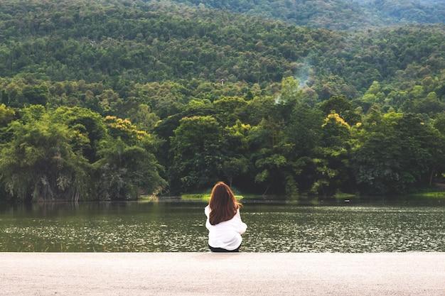 Uma mulher sentada sozinha à beira do lago, olhando as montanhas com a natureza nublada e verde