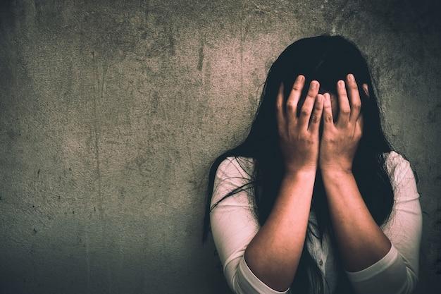 Uma mulher sentada sozinha e deprimida.