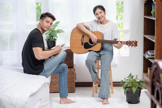 Uma mulher sentada toca violão e um homem segurando um livro e cantando.