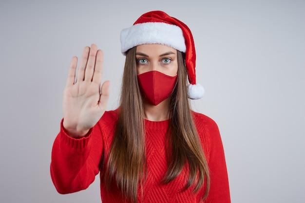 Uma mulher séria com uma máscara protetora e um chapéu de papai noel