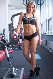 Uma mulher séria e esportiva, que usa shorts pretos justos e uma camiseta sem mangas, fica na ponta dos pés após um treino. uma garota loira fitness está posando em um ginásio.